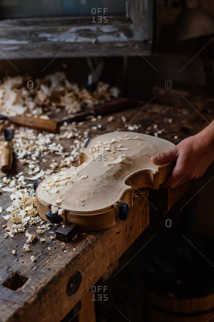 High angle of unrecognizable craftsman planing wooden violin soundboard using tool at table in work studio