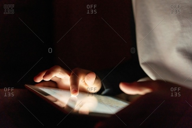 Anonymous crop kid in casual wear playing games on tablet while entertaining during weekend in apartment