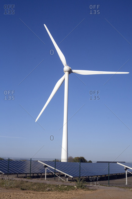 April 21, 2020: A wind turbine on Newton Down with photovoltaic solar panels on the ground, Newton Down, Porthcawl, South Wales, United Kingdom, Europe