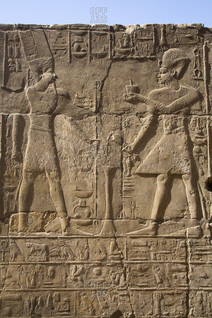 March 18, 2020: Pharaoh on right, God Amun on the left, Bas Relief, Luxor Temple, UNESCO World Heritage Site, Luxor, Thebes, Egypt, North Africa, Africa