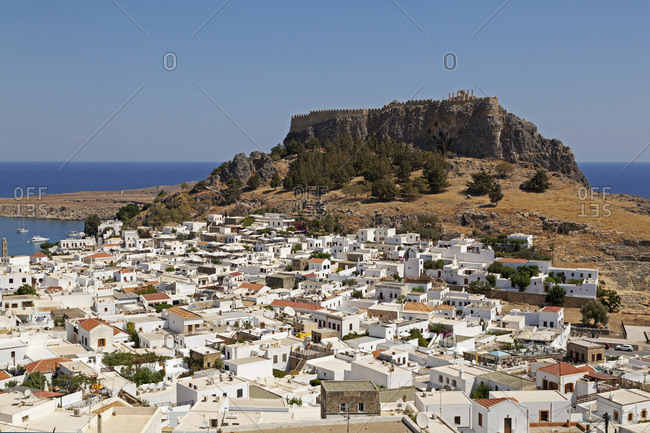 September 16, 2016: The Lindian Acropolis, site rises over white houses in the fishing village of Lindos on Rhodes, Dodecanese, Greek Islands, Greece, Europe