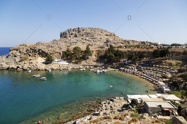 September 15, 2016: Sun shades line the beach at St. Paul's Bay on a sunny day in Lindos on Rhodes, Dodecanese, Greek Islands, Greece, Europe