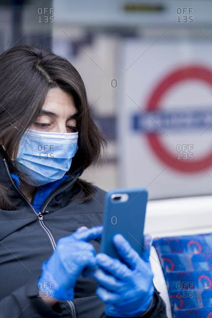 March 25, 2020: A woman wearing a protective hygiene (pollution) face mask on the London Underground subway system, London, England, United Kingdom, Europe