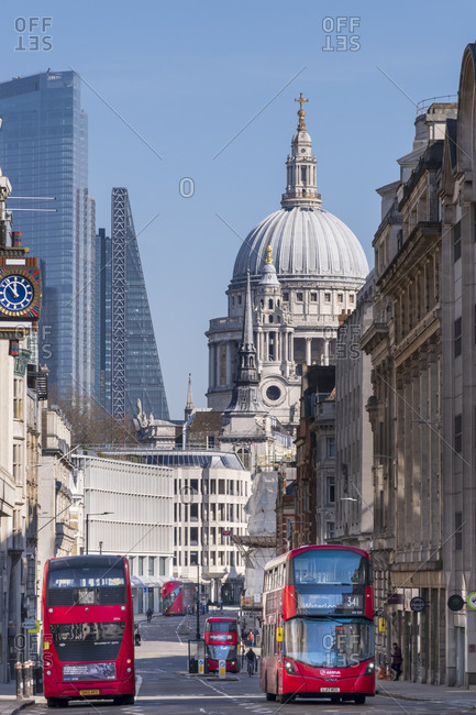 March 25, 2020: Red double-decker buses on Fleet Street with the dome of St. Paul's Cathedral and skyscrapers in the financial district of City of London, London, England, United Kingdom, Europe