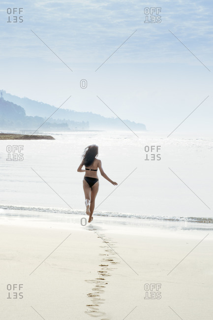 A woman solo traveller in a bikini running into the sea on a pristine tropical beach and leaving footprints, Indonesia, Southeast Asia, Asia