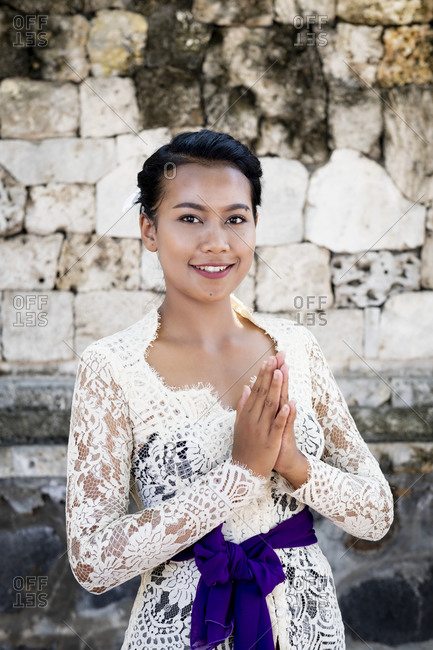 November 18, 2019: A young Balinese woman in a local temple dress making a formal greeting and smiling, Bali, Indonesia, Southeast Asia, Asia