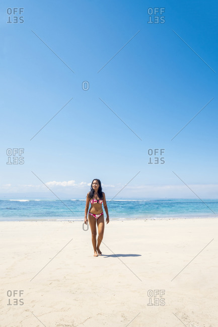 November 18, 2019: A beautiful Asian woman solo traveller in a bikini on a pristine tropical beach, Bali, Indonesia, Southeast Asia, Asia