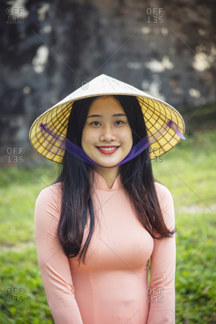 January 9, 2019: A young Vietnamese woman in a traditional Ao Dai dress and conical hat and smiling, Hue, Vietnam, Indochina, Southeast Asia, Asia