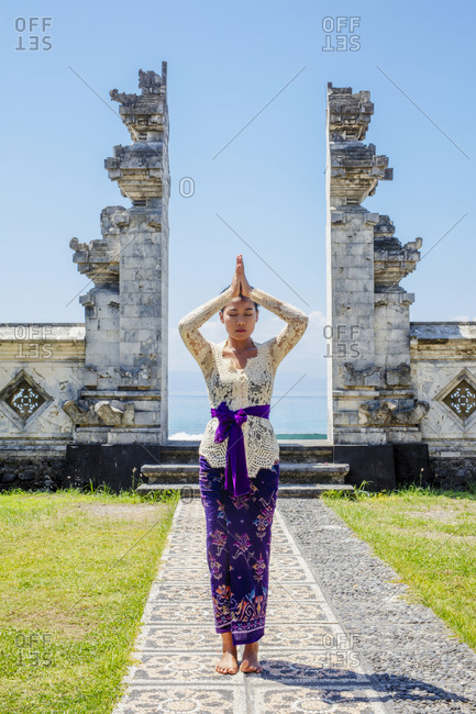 November 18, 2019: A young Balinese woman in traditional temple at the shoreside Pura Candidasa Hindu temple, Bali, Indonesia, Southeast Asia, Asia