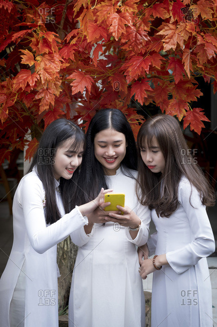 January 10, 2019: Three Vietnamese female friends wearing traditional Ao Dai dresses and sharing a mobile phone, Hue, Vietnam, Indochina, Southeast Asia, Asia