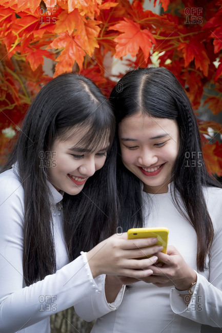 January 10, 2019: Two Vietnamese friends wearing traditional Ao Dai dresses and sharing a mobile phone, Hue, Vietnam, Indochina, Southeast Asia, Asia