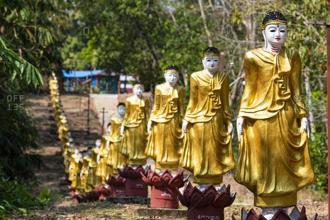 January 13, 2020: Long line of golden Buddhas lining up to Shwemawdaw Paya, Kyaing Ywar near Ye, Mon state, Myanmar (Burma), Asia