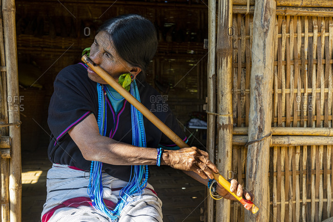February 4, 2020: Chin woman with spiderweb tattoo blowing a flute with her nose, Kanpelet, Chin state, Myanmar (Burma), Asia