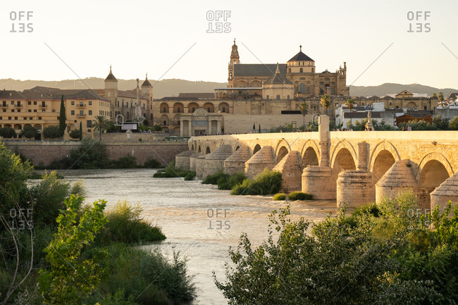 August 13, 2018: The Roman Bridge (Puente Romano) and The Great Mosque of Cordoba in the glow of sunset at golden hour, UNESCO World Heritage Site, Cordoba, Andalusia, Spain, Europe