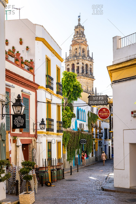 August 14, 2018: The Bell Tower of Cordoba Mosque Cathedral seen through a typical Andalusian street, Cordoba, Andalusia, Spain, Europe