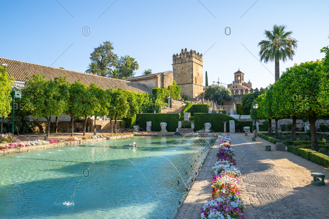 August 15, 2018: Lion Tower and a pond with fountains in the gardens of the Alcazar de Los Reyes Cristianos, UNESCO World Heritage Site, Cordoba, Andalusia, Spain, Europe