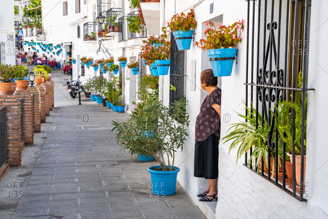 August 18, 2018: An elderly woman stands in front of a whitewashed house covered in blue plant pots in Mijas Pueblo, Andalusia, Spain, Europe