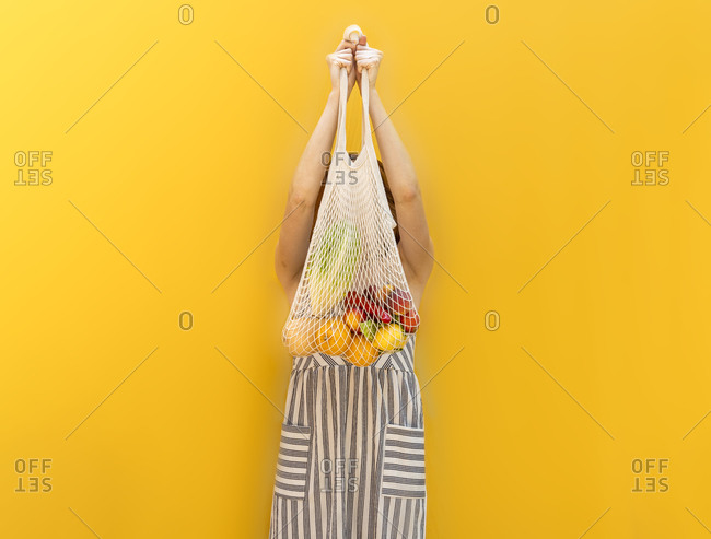 Young woman holding fruits in mesh bag while standing against yellow background