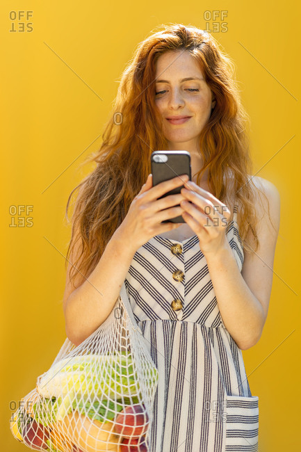Smiling young woman using smart phone while standing against yellow background