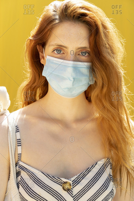 Close-up of young woman wearing face mask against yellow background