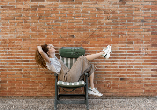 Thoughtful woman with hands in hair relaxing on chair against brick wall