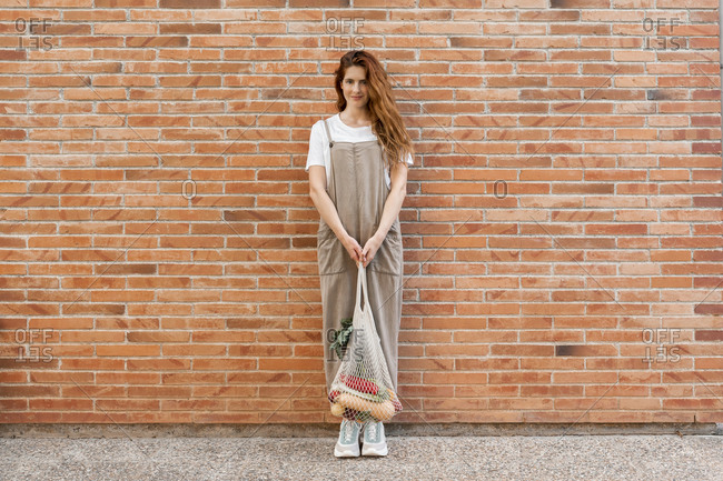 Young woman with long hair holding groceries in mesh bag while standing against brick wall