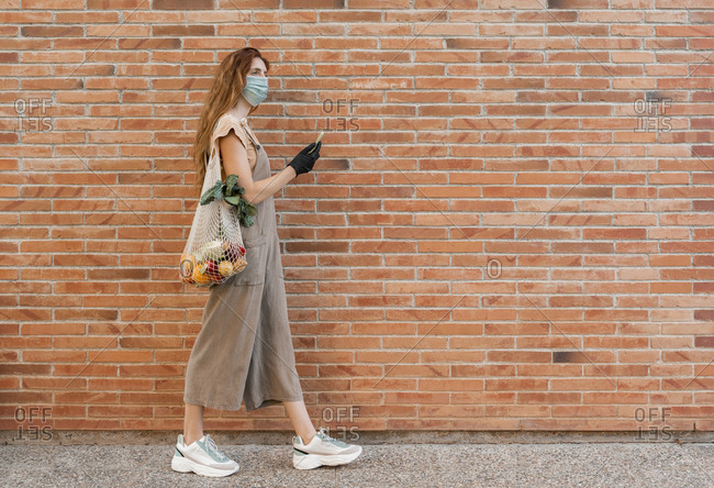Young woman wearing mask using smart phone while walking on footpath by brick wall