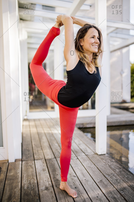 Smiling woman practicing dancer pose on hardwood floor against house