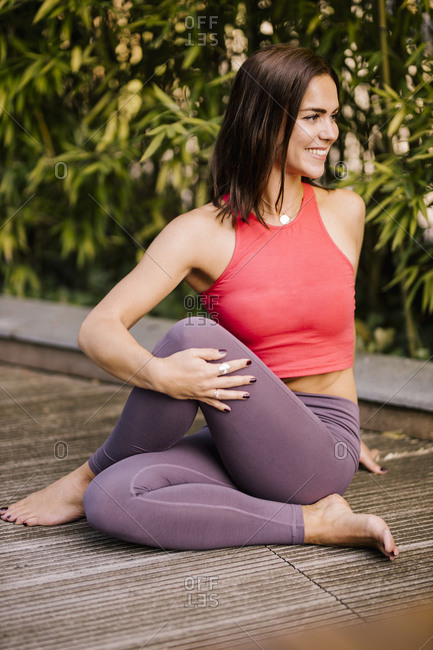 Smiling woman exercising while sitting on hardwood floor against plants