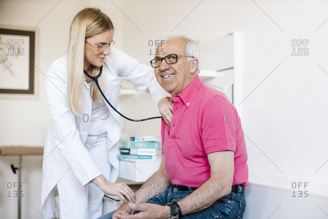 Female doctor examining senior patient in medical clinic