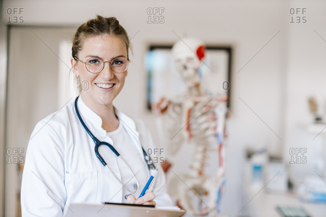 Portrait of smiling female doctor with anatomical skeleton in the background