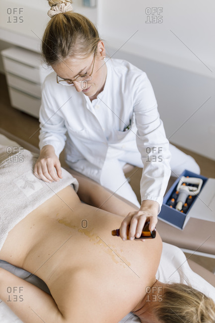 Cupping therapy- female alternative practitioner applying oil for treatment at back