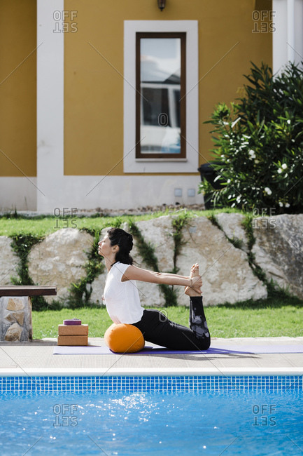 Woman practicing bow pose while leaning on bolster at poolside in yard
