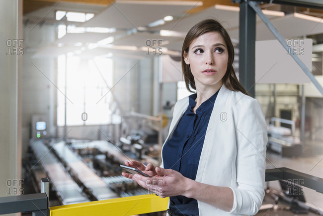 Female manager holding digital tablet looking away while standing in factory