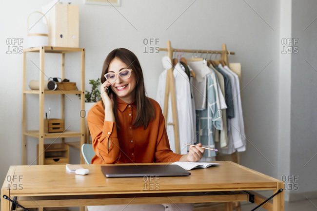 Female fashion designer sitting at desk in home office talking on the phone