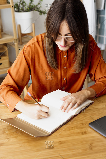 Female freelancer working at home sitting at desk taking notes