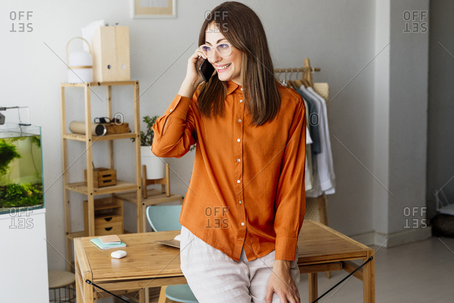 Female fashion designer in home office talking on the phone