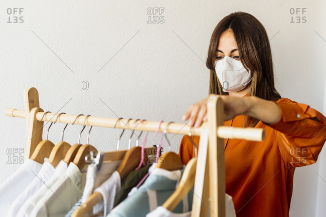 Female fashion designer working at home with clothes stand wearing protective face mask