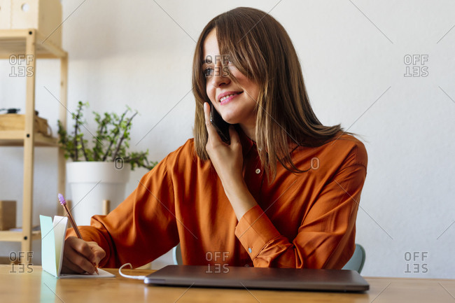 Female freelancer sitting at desk in home office talking on the phone and taking notes