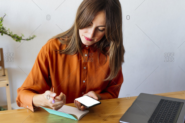 Female freelancer working at home sitting at desk with notepad and smartphone