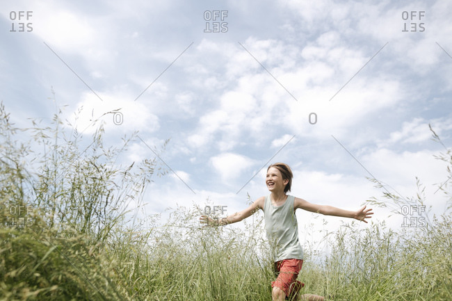 Portrait of happy boy running on a field with arms outstretched