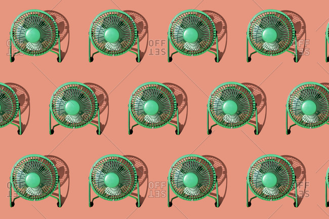 Green electric fans against orange background