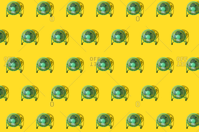 Green electric fans against yellow background