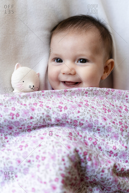 Portrait of happy baby girl lying on bed with teether