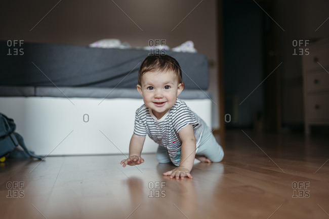 Portrait of smiling baby girl crawling on floor of bedroom
