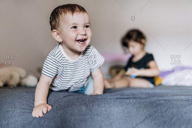 Portrait of happy baby girl crawling on  bed while her sister sitting in the background
