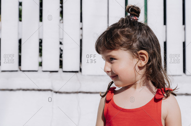 Portrait of little girl wearing red summer dress in front of white wall