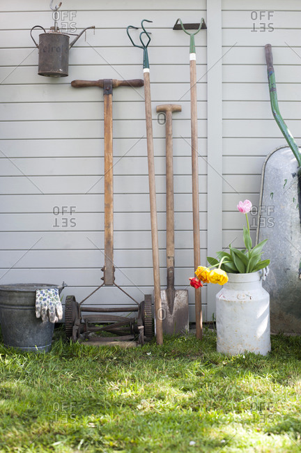 Various gardening tools leaning on shed wall
