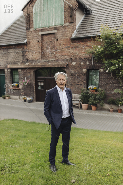 Portrait of a senior businessman standing in front of a farmhouse