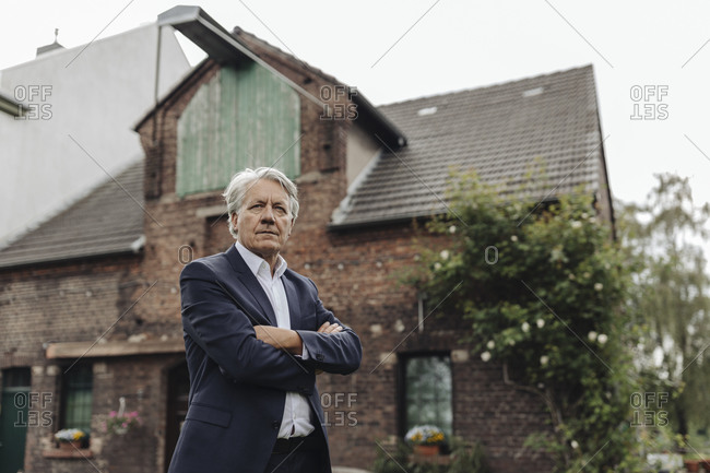 Portrait of a senior businessman in front of a farmhouse